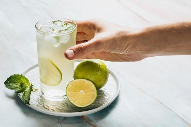 Lemonade glass and limes on bamble background Free Photo