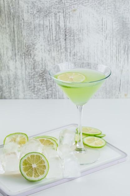 Лимонад в стакане с лимоном, разделочная доска, кубики льда, вид сбоку на белый и шероховатый Бесплатные Фотографии
