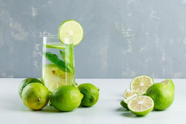 Лимонад в стакане с лимонами, вид сбоку травы на белом и гипса Бесплатные Фотографии