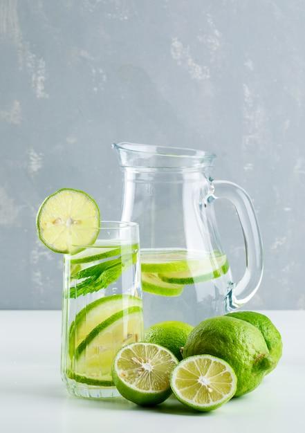 Лимонад в стакане и кувшин с лимоном, базилик вид сбоку на белый и гипс Бесплатные Фотографии
