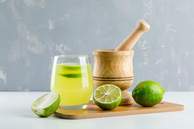 Лимонад с лимоном, ступкой и пестиком, разделочная доска в стакане на белом и гипс, Бесплатные Фотографии