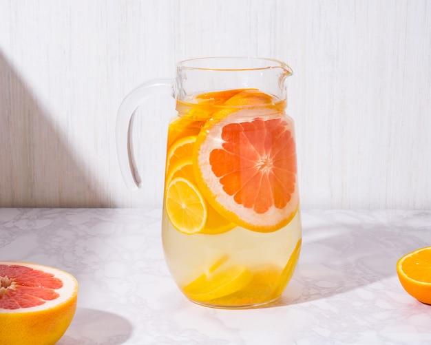 Лимонад с лимонами и грейпфрутом в стеклянной банке на белом фоне. холодный летний освежающий напиток или напиток Premium Фотографии