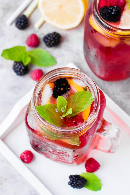 Lemonade with raspberry and blackberry with lemon, mint in mason jar Premium Photo