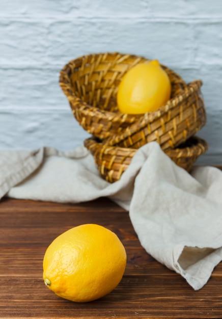 Limoni in ceste su una superficie di legno. vista dall'alto. spazio per il testo Foto Gratuite