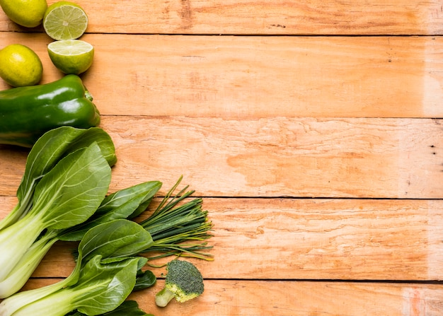 Lemons; bell peppers; broccoli; chives and bokchoy on wooden plank Free Photo