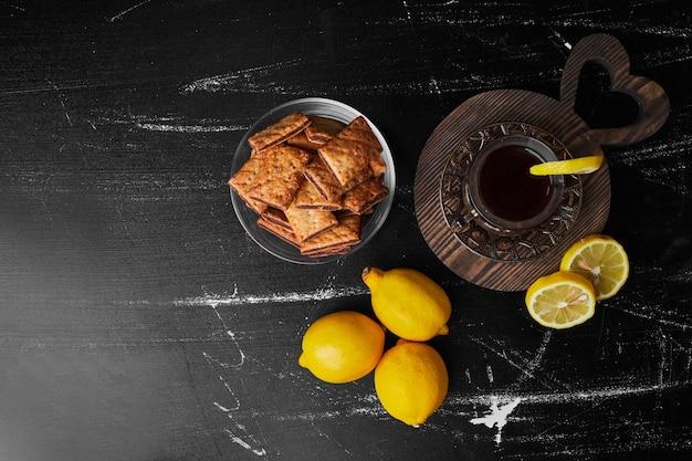 Limoni isolati su uno sfondo nero con un bicchiere di tè e cracker. Foto Gratuite