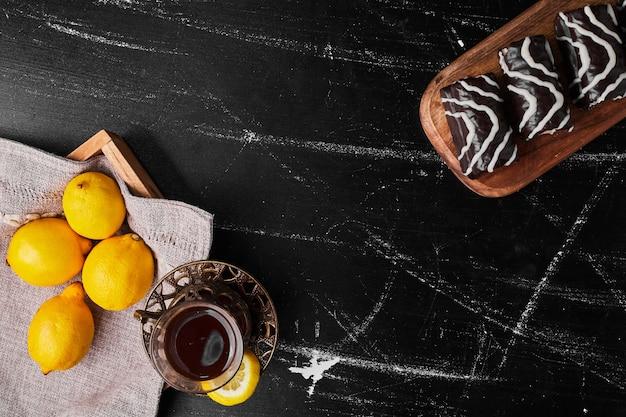 Limoni isolati su uno sfondo nero con pasticcini e tè. Foto Gratuite