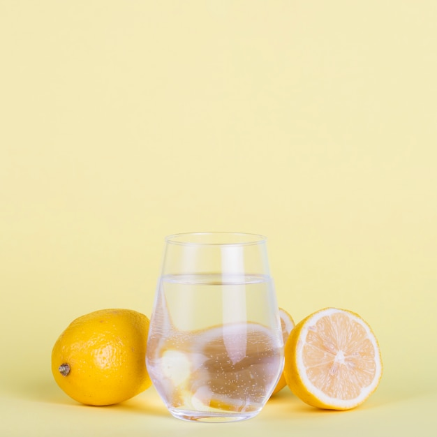Lemons and water on yellow background Free Photo