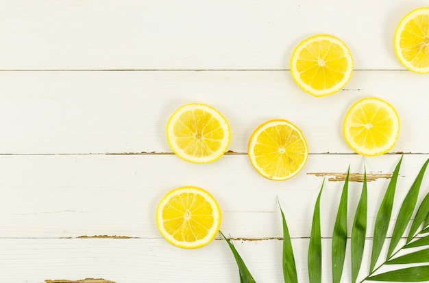 Lemons with palm leaf on table Free Photo