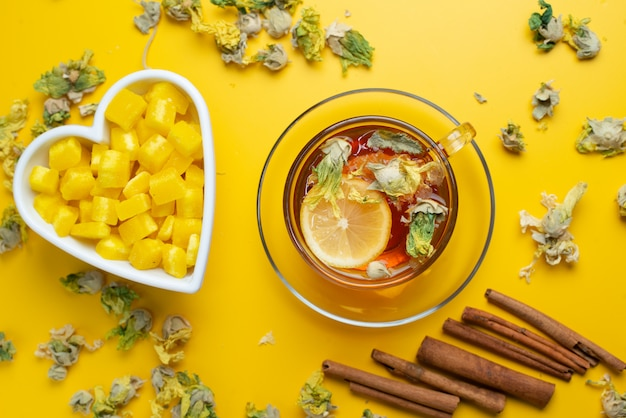 乾燥ハーブ、砂糖の立方体、シナモンスティックレモンティーをカップの黄色い表面に平らに置きます。 無料写真