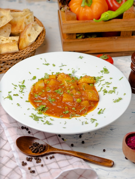 Lentil cream soup with potato and tomato sauce and vegetables , served with lavash in white plate Free Photo