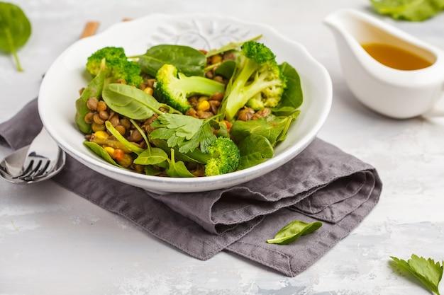 Салат карри из чечевицы с брокколи и авокадо на белом Premium Фотографии