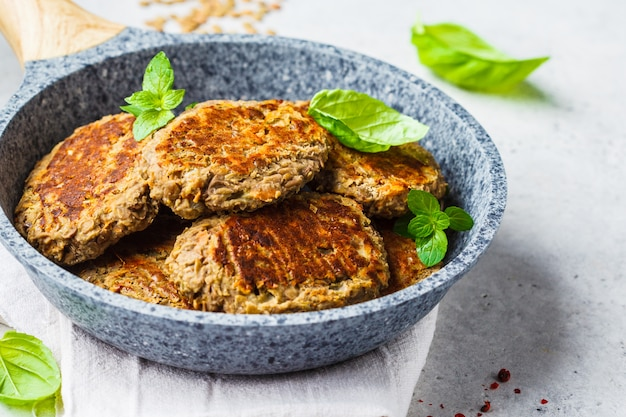 Lentil patties in gray frying pan. healthy vegan food concept. Premium Photo
