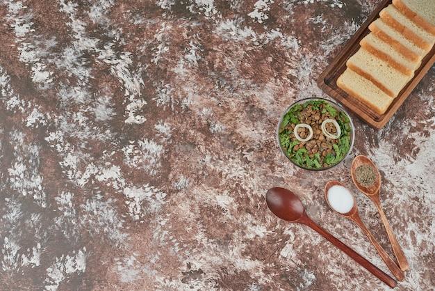 ハーブとパンとガラスのカップのレンズ豆のサラダ。 無料写真