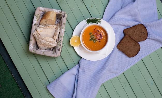 Zuppa di lenticchie servita con fette di pane e limone su un tavolo blu Foto Gratuite
