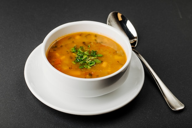 Lentil soup with mixed ingredients and herbs in a white bowl with a spoon. Free Photo