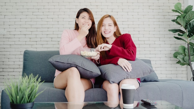 Lesbian asian couple watching tv laugh and eating popcorn in living room at home, sweet couple enjoy Free Photo