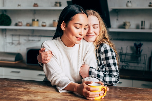 Lesbian couple embracing in kitchen Free Photo