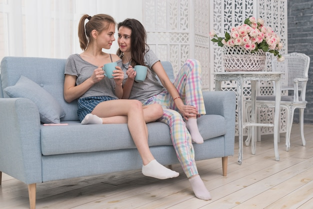 Lesbian couple holding cup of coffee sitting on sofa looking at each other Free Photo