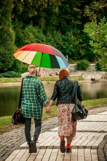 手を繋いでいるレズビアンのカップルは、虹の傘で雨の中で秋の公園を散歩します。 Premium写真