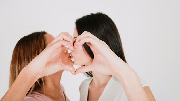 Lesbian couple kissing and gesturing heart Free Photo