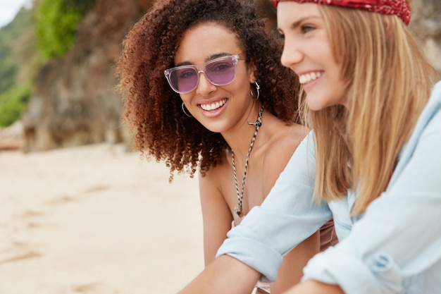 Лесбийская пара или близкие молодые подруги отдыхают на тропическом пляже, смотрят на солнечный свет с довольным выражением лица, рассказывают настоящую историю любви. Бесплатные Фотографии