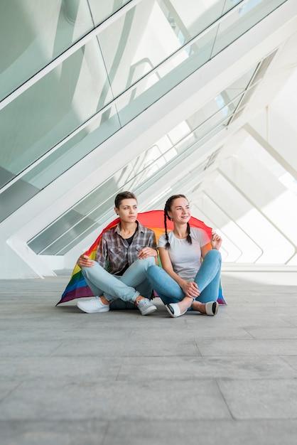 Lesbian couple sitting on paving stone Free Photo