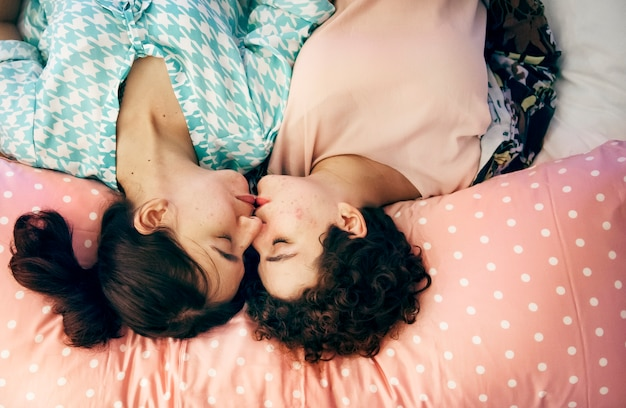 Lesbian couple sleeping on the bed together Free Photo