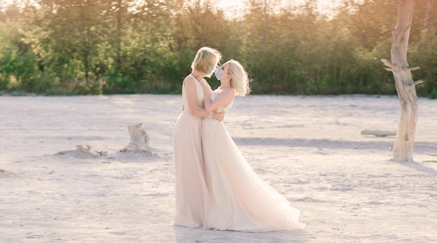 Lesbian couple wedding on white sand, wear masks to prevent epidemic covid-19 Premium Photo