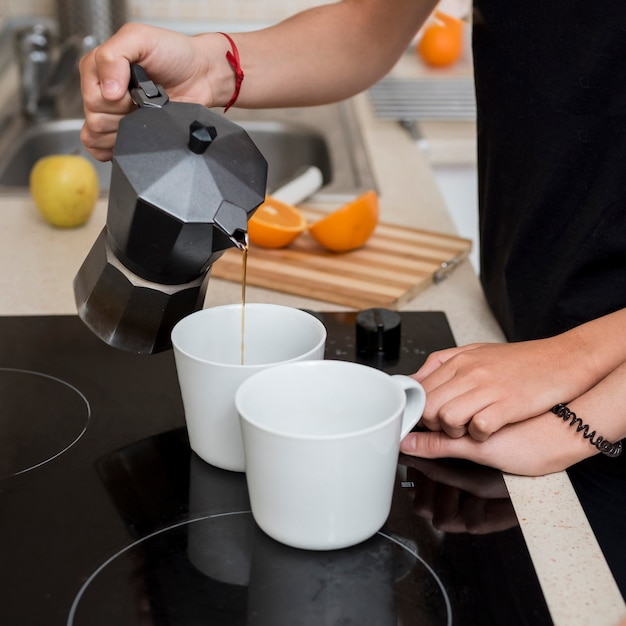 Lesbian woman pouring coffee in kitchen Free Photo