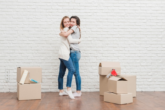 Lesbian young couple embracing each other in their new house against white brick wall Free Photo
