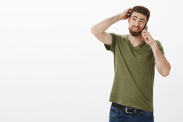 考えさせて。スマートフォン経由で友達に話しているように計画を立てているひげを持つかわいい男 無料写真