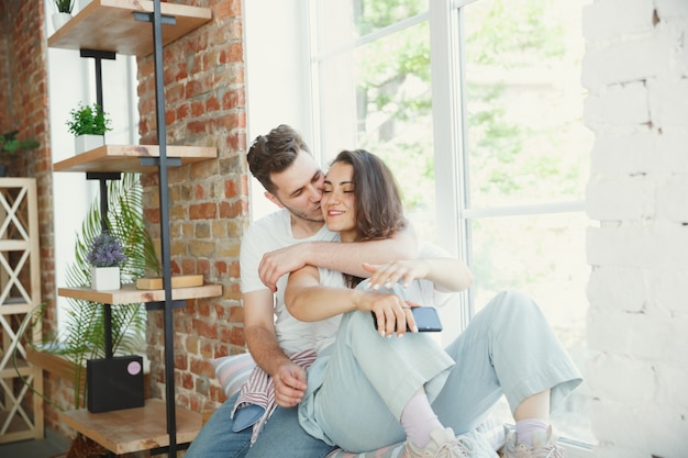 Let's catch this moment. young couple moved to a new house or apartment. look happy and confident. family, moving, relations, first home concept. sitting near by window, hugging and making selfie. Free Photo