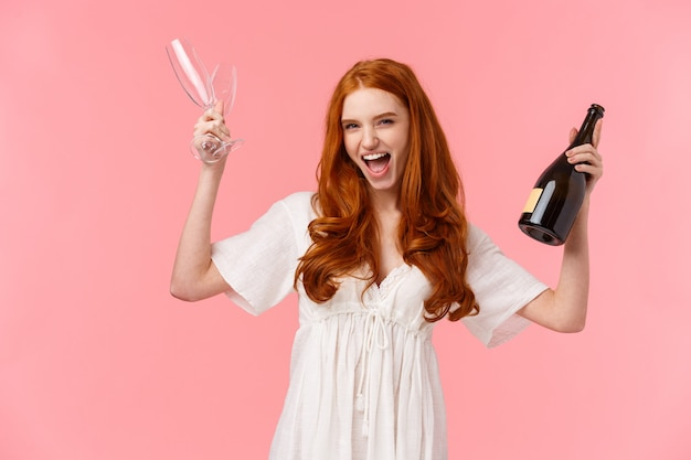 Lets get this party started, girls night. cheerful and excited good-looking redhead woman having fun on bachelorette night before wedding, scream joyfully, raise glasses and champagne bottle Premium Photo