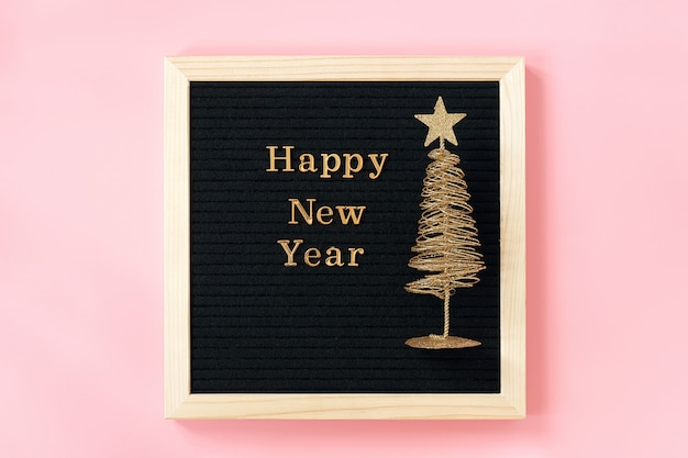 Letter board with golden text happy new year and shiny christmas tree on pink wall Premium Photo