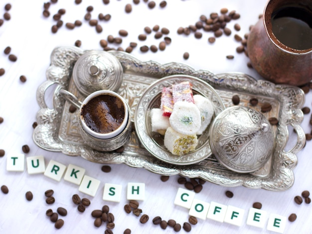 Lettering turkish coffee with traditional turkish sweets in a silver mug Premium Photo