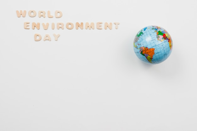 Letters in phrase world environment day beside globe Free Photo