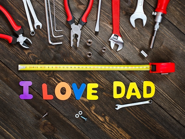 Letters and tools on a wooden background father's day Premium Photo