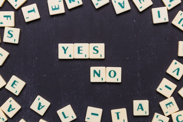 Letters yes or no made from scrabble game letters against black background Free Photo