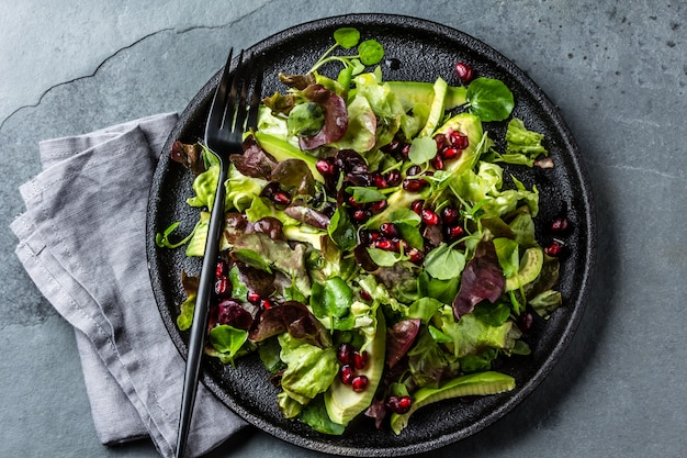 Lettuce salad with pomegranate on black plate. Premium Photo