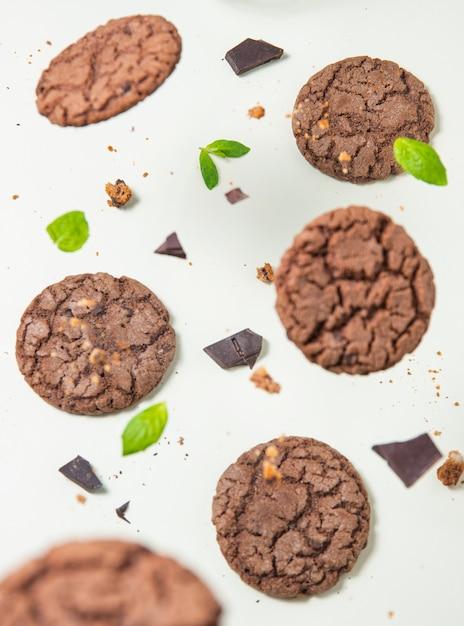 Шоколадное домашнее печенье с листьями мяты на желтом фоне. вид сверху Premium Фотографии