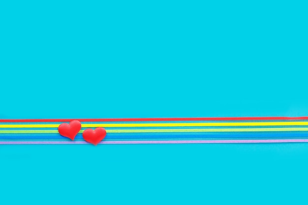 Lgbt community pride rainbow ribbon awareness and two hearts on blue Premium Photo