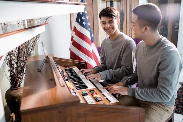 Lgbt男性同性愛者がピアノを弾いています。彼の恋人と幸せに Premium写真