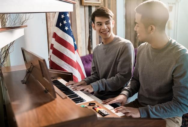 Lgbt男性同性愛者がピアノを弾いています。彼の恋人と喜んで Premium写真