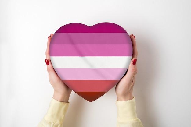 女性の手でハート形ボックスにlgbtレズビアンプライドフラグ。プライドシンボル。上面図 Premium写真
