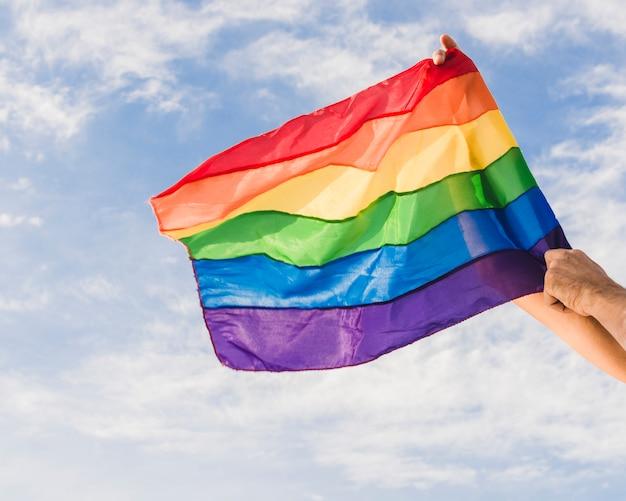 Lgbt色と雲と青い空の大きな旗を持つ男 無料写真