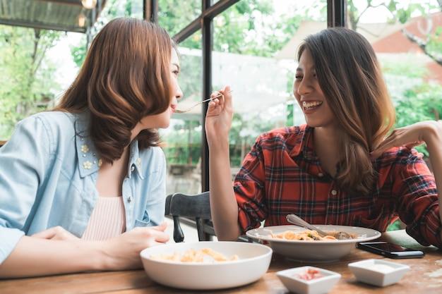 美しい幸せなアジアの女性レズビアンのlgbtカップルは、イタリアのシーフードのプレートを食べる両側に座って 無料写真