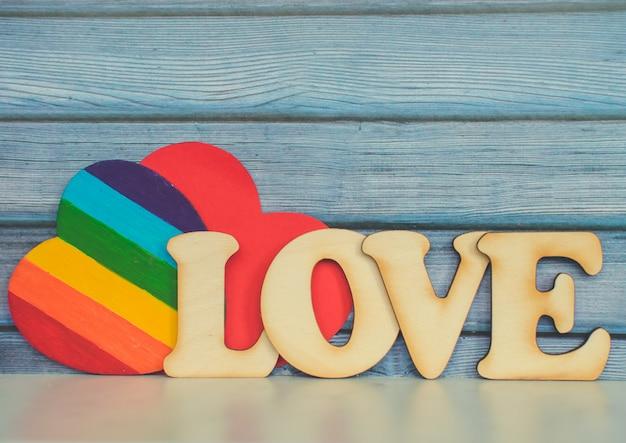 Предпосылка карточки дня валентинок, сердце радуги милое как флаг радуги гордости lgbt с красным бумажным сердцем и декоративным деревянным словом. день святого валентина романтичный. любовь концепции прав человека и свободы. Premium Фотографии