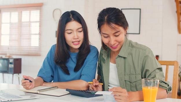 ビジネスアジアのレズビアンlgbtq女性カップルは自宅でアカウントを行います 無料写真