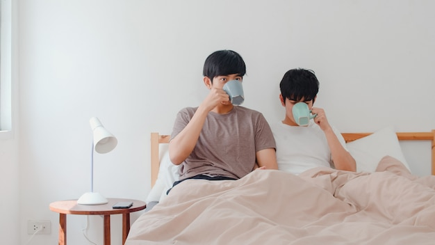 現代の家で素晴らしい時間を過ごして話しているアジアのゲイの男性カップル。若いアジアの恋人lgbtq +男性の幸せは、朝の家の寝室のベッドの上に横たわっている間目を覚ます後休憩コーヒーをリラックスします。 無料写真